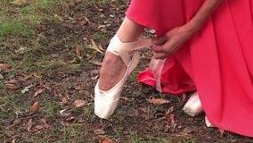 Ballerina som binder pointeskor som sitter yttersidan lager videofilmer