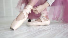 Ballerina som binder pointesna bärande balettskor för balettdansör i studion stock video