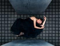 Ballerina som ligger på grå färgtegelplattor mellan tjock skiva Arkivbilder
