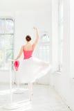 Ballerina som poserar i pointeskor på den vita träpaviljongen Arkivbild