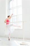 Ballerina som poserar i pointeskor på den vita träpaviljongen Arkivfoto