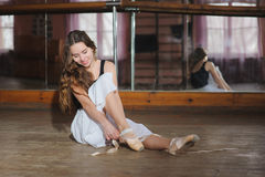 Ballerina som sätter på hennes balettskor Arkivfoto