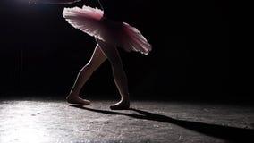 Ballerina som utför piruetter på svart bakgrund i studio Bärande ballerinakjol- och pointeskor för kvinnlig balettdansör långsamt lager videofilmer