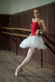 Ballerina standing near the bar on tiptoe. Leaning his elbow Stock Photo