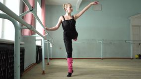 Ballerina at the Barre. Ballerina standing on poite at barre in ballet class stock footage