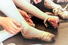 Ballerina strength in delicate feet. Npreparing to enter the stage with all delicate feetnwith pink ribbons and socks stock image