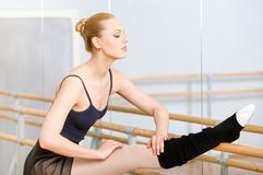 Ballerina stretches herself near barre Stock Photos