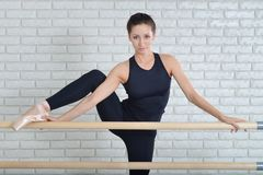Ballerina stretches herself near barre at ballet studio, close up portrait of beautiful woman dancer looking at camera. Stock Photo