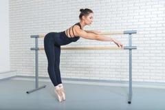 Ballerina stretches herself near barre at ballet studio, full length portrait. Stock Image