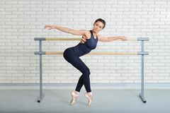 Ballerina stretches herself near barre at ballet studio, full length portrait.