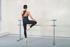 Ballerina stretches herself near barre at ballet studio, full length portrait, shoot from behind. Royalty Free Stock Photography