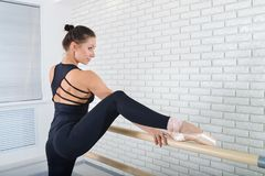 Ballerina stretches herself near barre at ballet studio, three quarter length portrait.
