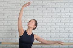 Ballerina stretches herself near barre in the classroom, beautiful women weared in black bodysuit practicing ballet Stock Photos