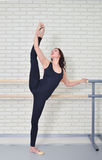 Ballerina stretches herself near barre in the classroom, beautiful women weared in black bodysuit practicing ballet