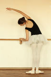 Ballerina. Stretches herself near barre and wall in the classroom Royalty Free Stock Image