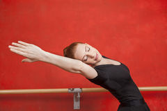 Ballerina Stretching Against Red Wall Royalty Free Stock Photo