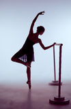 Ballerina stretching on the bar Stock Photos