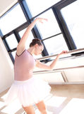 Ballerina Stretching at Barre in Dance Studio Stock Images