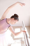 Ballerina Stretching at Barre in Dance Studio Stock Image