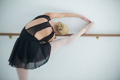 Ballerina stretching on a barre while practicing ballet dance Stock Images