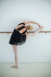 Ballerina stretching on a barre while practicing ballet dance Stock Image