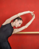 Ballerina Stretching With Hands Raised Against Red Wall Royalty Free Stock Photography