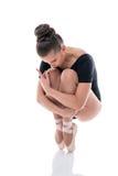 Ballerina sui pointes, innestanti le sue ginocchia al petto immagini stock