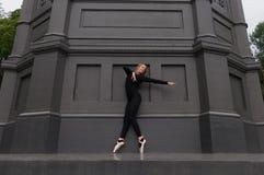 Ballerina sul pointe dell'en della punta dei piedi vicino alla parete nera Immagini Stock Libere da Diritti