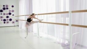 Ballerina sveglia che allunga mentre tenendo la sbarra di balletto stock footage
