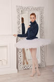 Ballerina in a sweater and a tutu. Pretty young ballerina standing in front of a mirror. A girl wearing a tutu and a black sweater Stock Photos