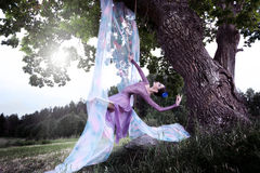 Ballerina is swinging on the trees of the old oak Stock Image