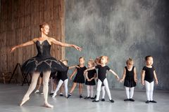 Ballerina teach girls. Young beautiful blonde female ballerina in black scenic tutu, bulky pantyhose and pointe shoes teaches little inattentive girls in black Stock Photo