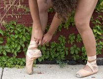 Ballerina ties her pointe shoes on city street royalty free stock photography