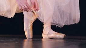 Female hands lace up two ribbons on ballet shoes. A ballerina ties her shoes and hides the knot under ribbons stock video
