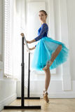 Ballerina is training on barre. Amazing ballerina stands on the right toe next to the ballet barre on the white wall background. She wears a lace blue leotard Stock Image