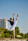 Ballerina in tutu dancing on the waterfront. Stock Photos