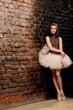 Ballerina in tutu near brick wall Stock Photo