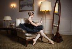 Ballerina in tutu nero che si siede davanti allo specchio Immagini Stock Libere da Diritti