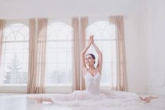 A ballerina on a twine in white clothes in a white studio. A ballerina on a twine in white clothes in a white light studio stock images