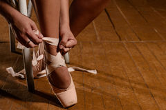 Ballerina tying ballet shoes sitting on the stage stock image