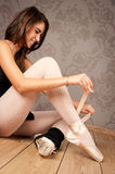 Ballerina tying her ballet slippers Royalty Free Stock Photo