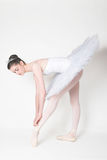 Ballerina Tying her Shoe. Ballerina wearing a white tutu, tying her shoe royalty free stock photo