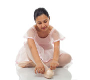 Ballerina while tying his shoes for dancing. royalty free stock photos