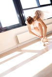 Ballerina Tying Laces of Ballet Slippers in Studio Royalty Free Stock Photos