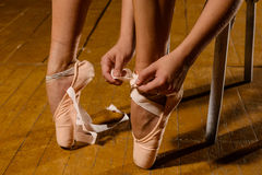 Ballerina tying pointe ballet shoes on stage Stock Images