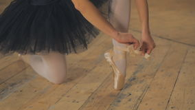 Ballerina tying pointe ballet shoes on stage. Beautiful Young Woman Ballerina Tying Pointe Shoes On The Background Of Wooden Wall stock footage