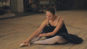 Ballerina tying pointe ballet shoes on stage. Beautiful Young Woman Ballerina Tying Pointe Shoes On The Background Of Wooden Wall stock video footage