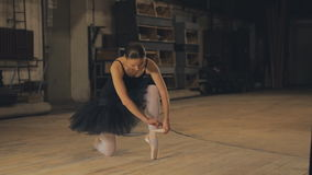 Ballerina tying pointe ballet shoes on stage. Pretty young ballerina in pointe puts stock video