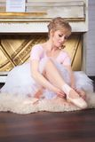 Ballerina tying pointe shoes Stock Photos