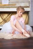 Ballerina tying pointe shoes Stock Photos